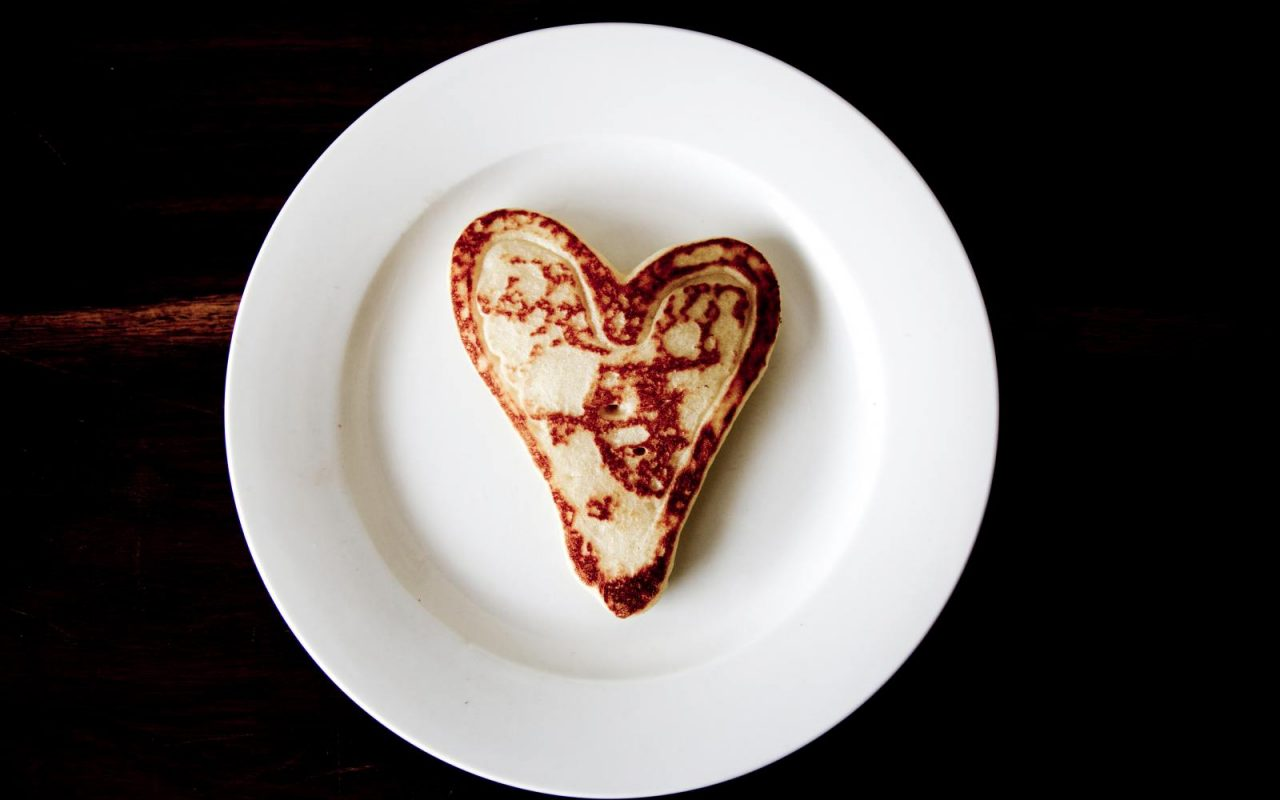 heart shaped toast on white plate black background