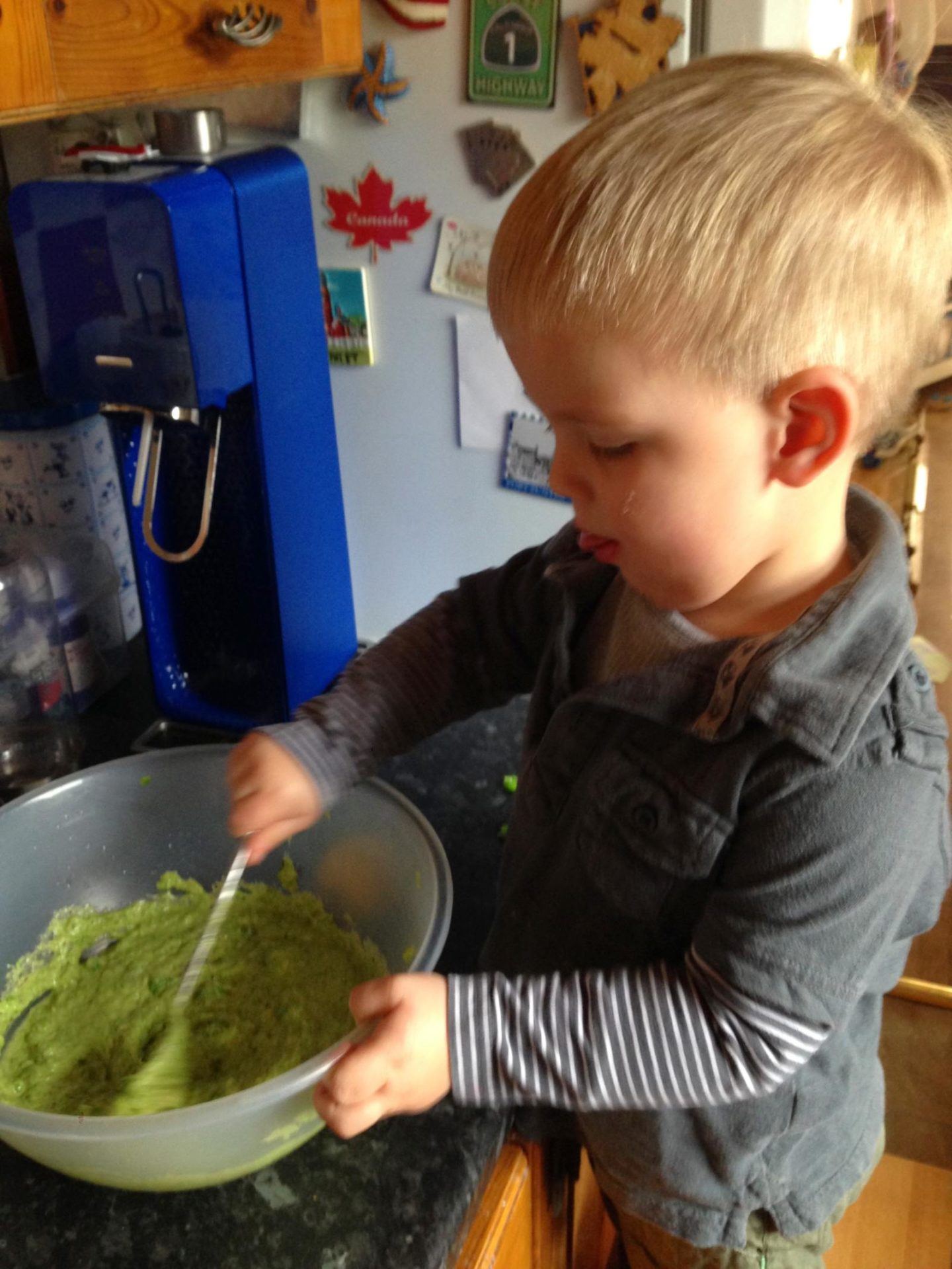 Toddler making pea fritters
