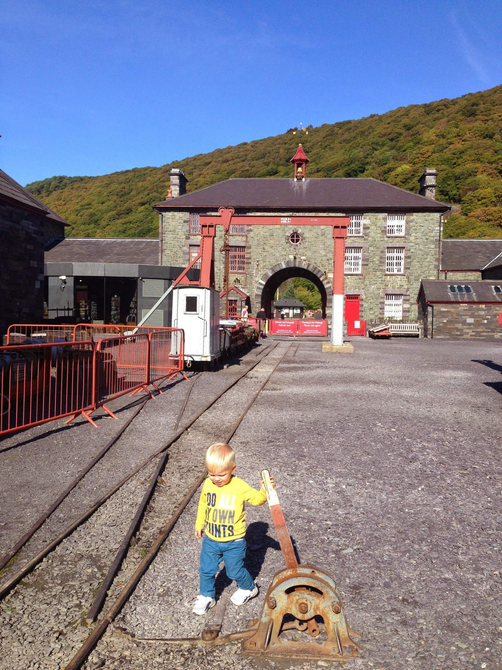 in the yard of the National Slate Museum in Wales on a day out with a toddler