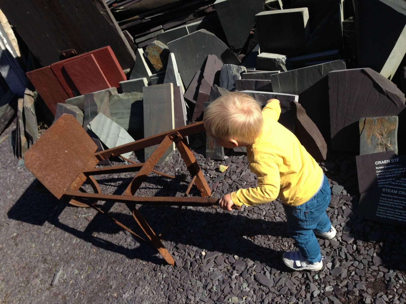 A toddler pushing a wheelbarrow at the National slate Museum in Wales