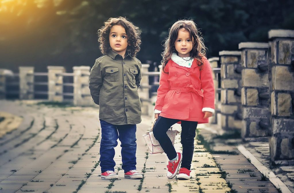 boy and girl toddlers standing outside wearing coats and jeans