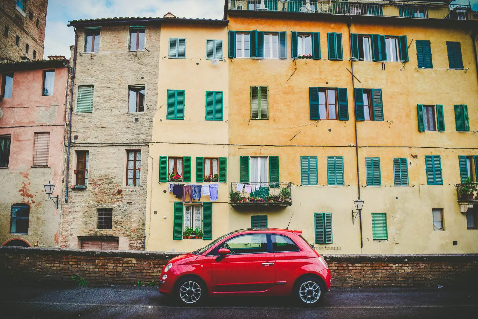 red car in front of buildings