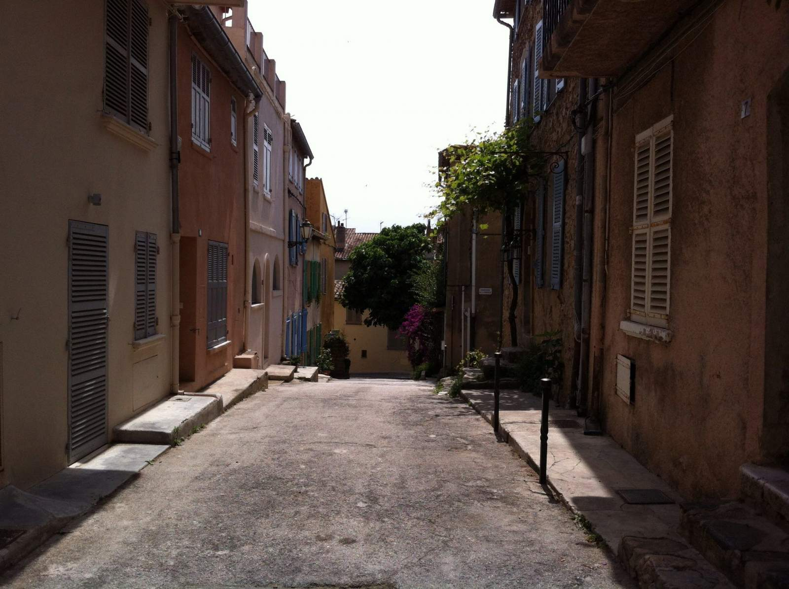 saint tropez town street with colourful houses both sides of road