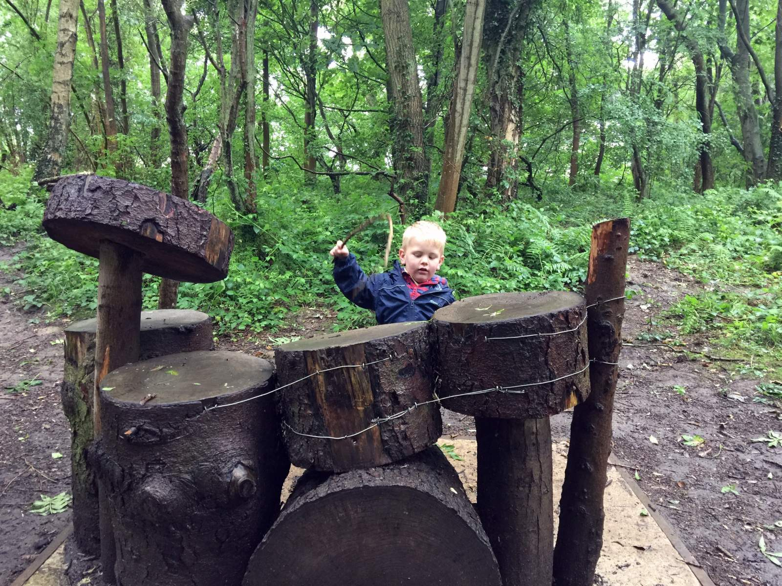 rainy day playing wooden drums at forest school in plessey woods