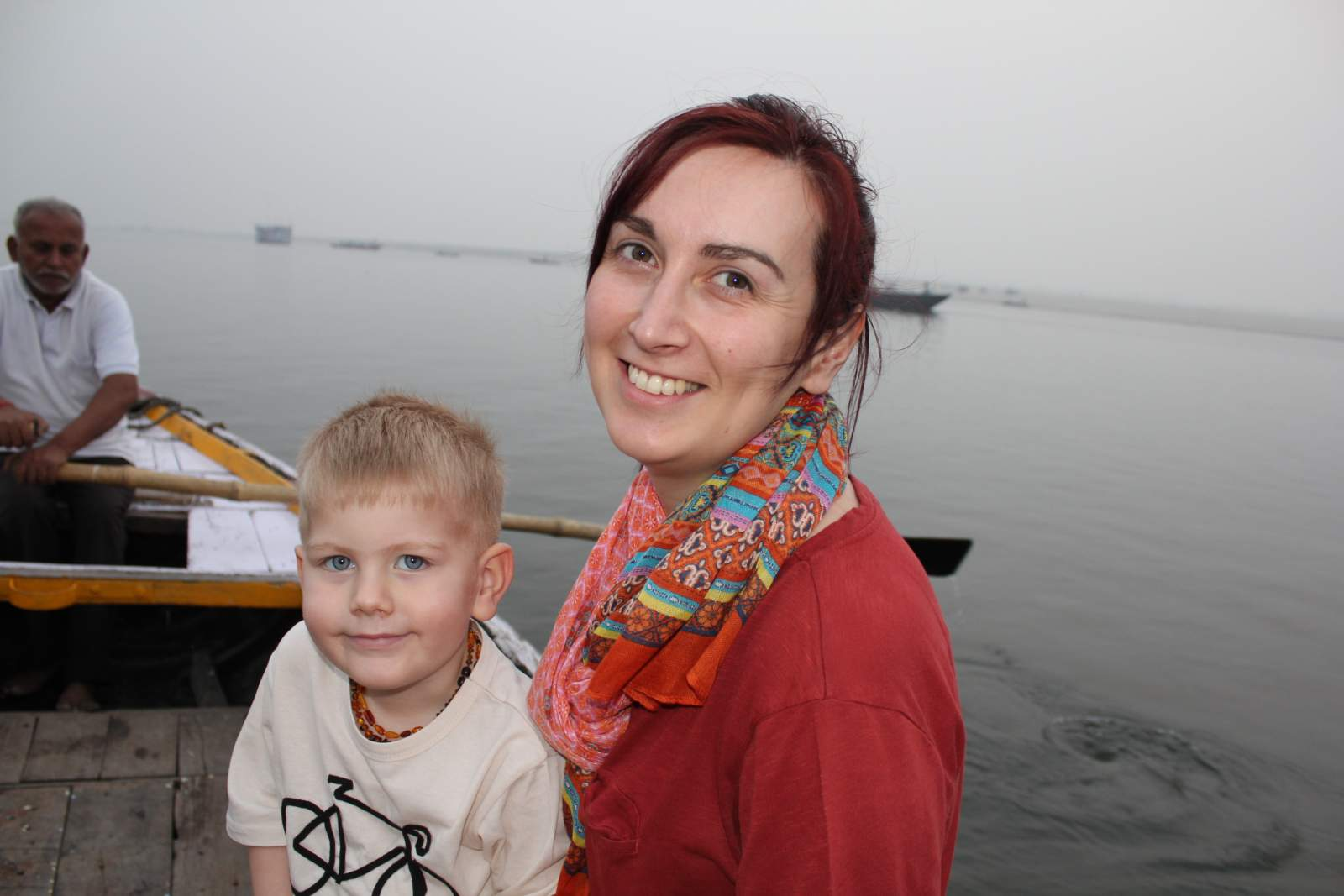 mother and son smiling on a boat on the ganges in varanasi India in February 2018