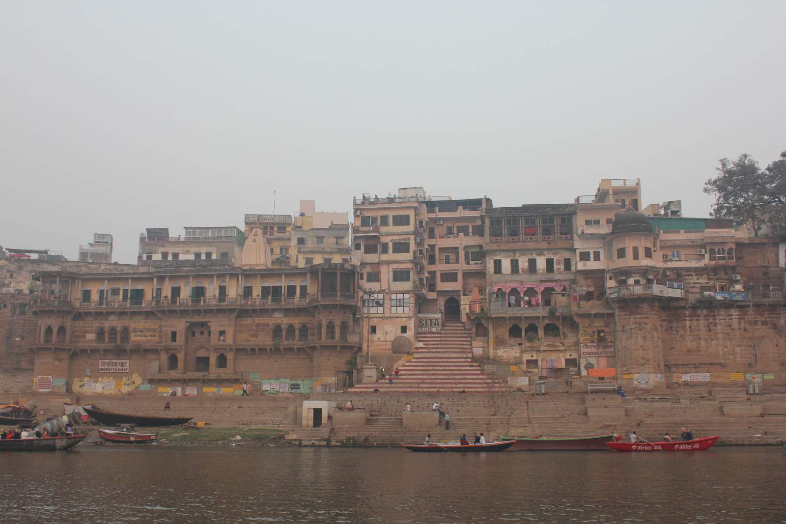 red boats on the ganges river in varanasi and pink stoned buildings