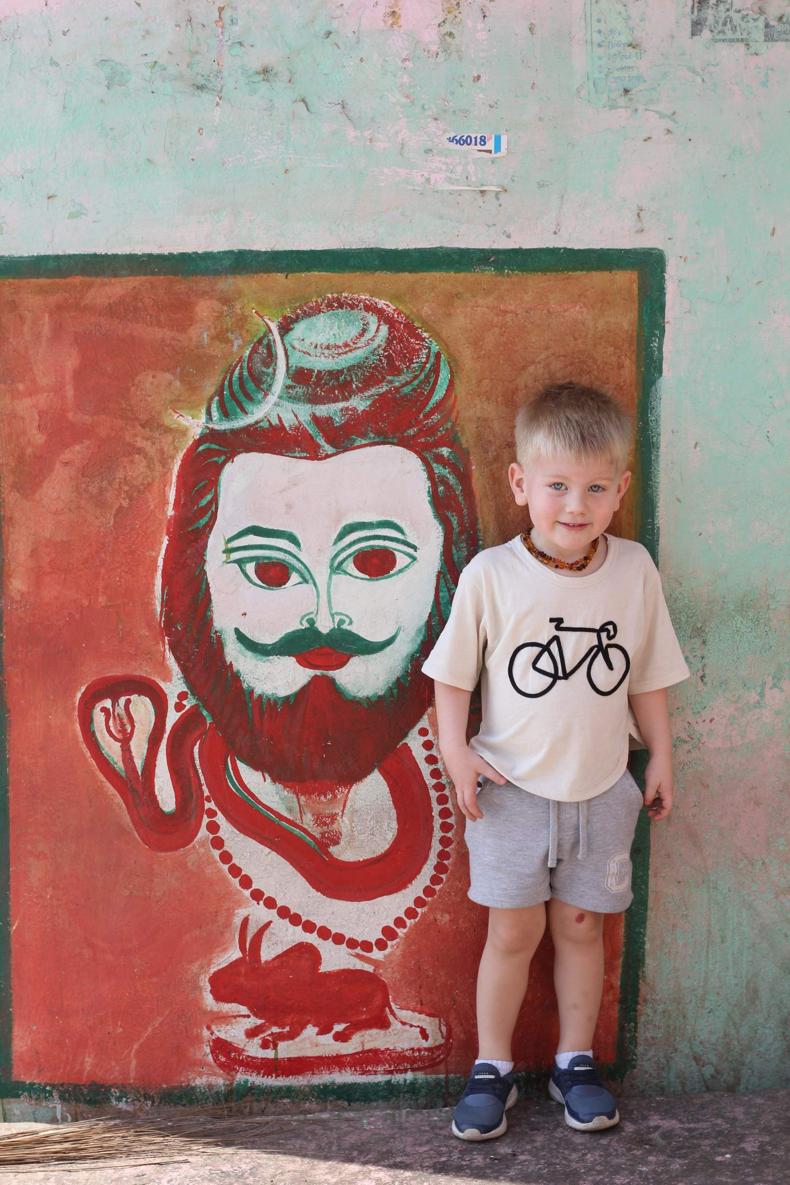 boy standing next to wall art in varanasi iNdia