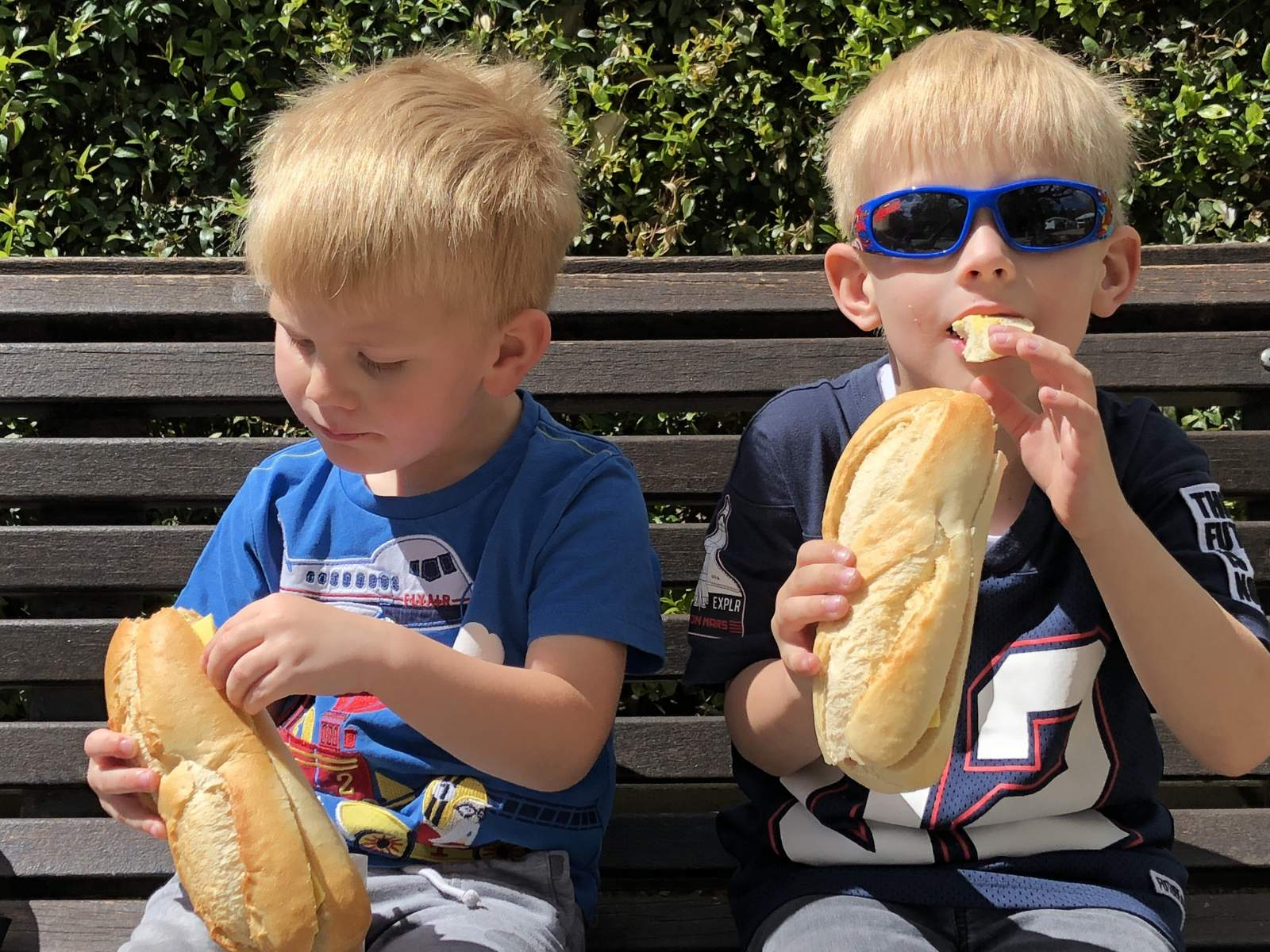 two boys enjoy crusty bread sandwiches in paloma park benalmadena