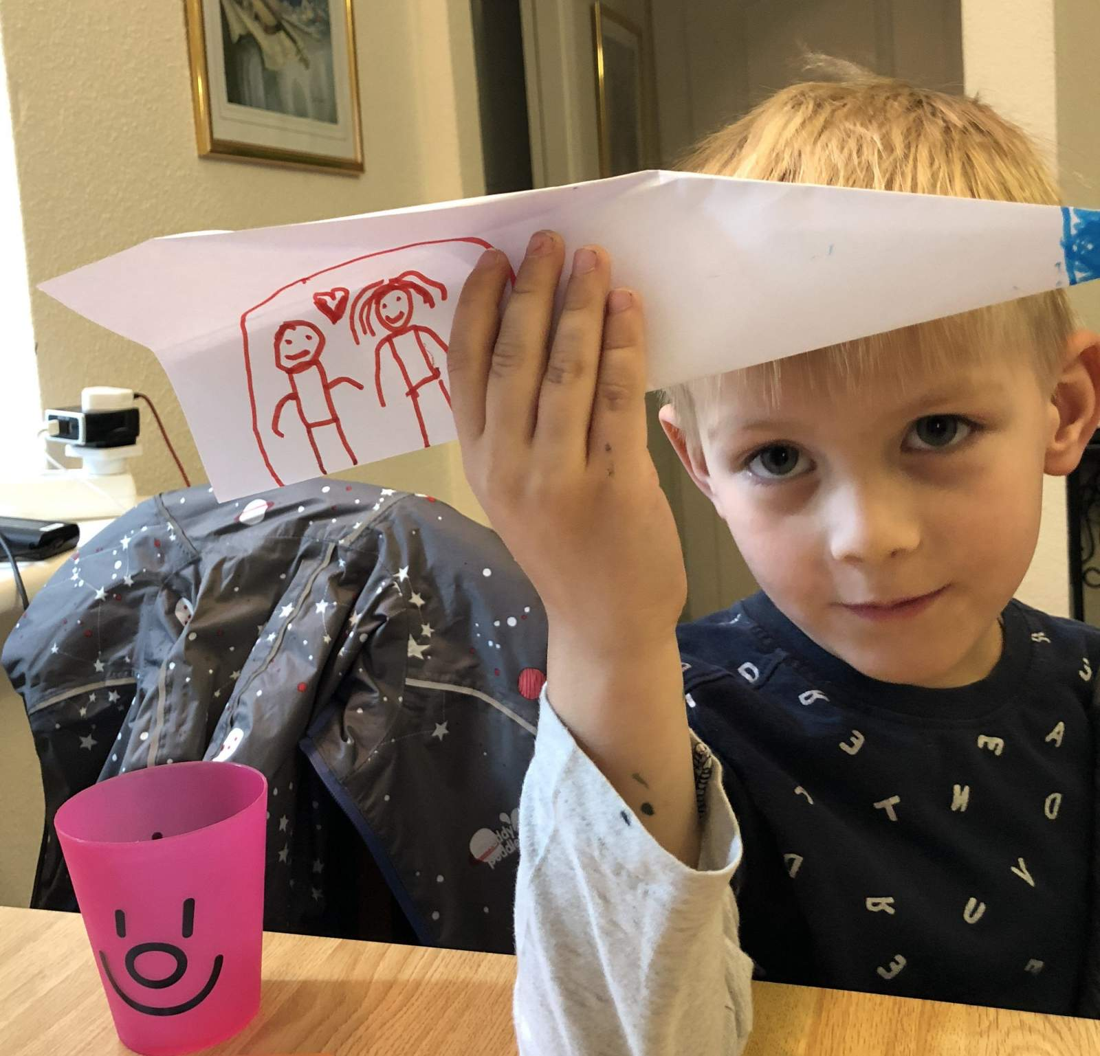 boy with paper aeroplane with people drawn on.