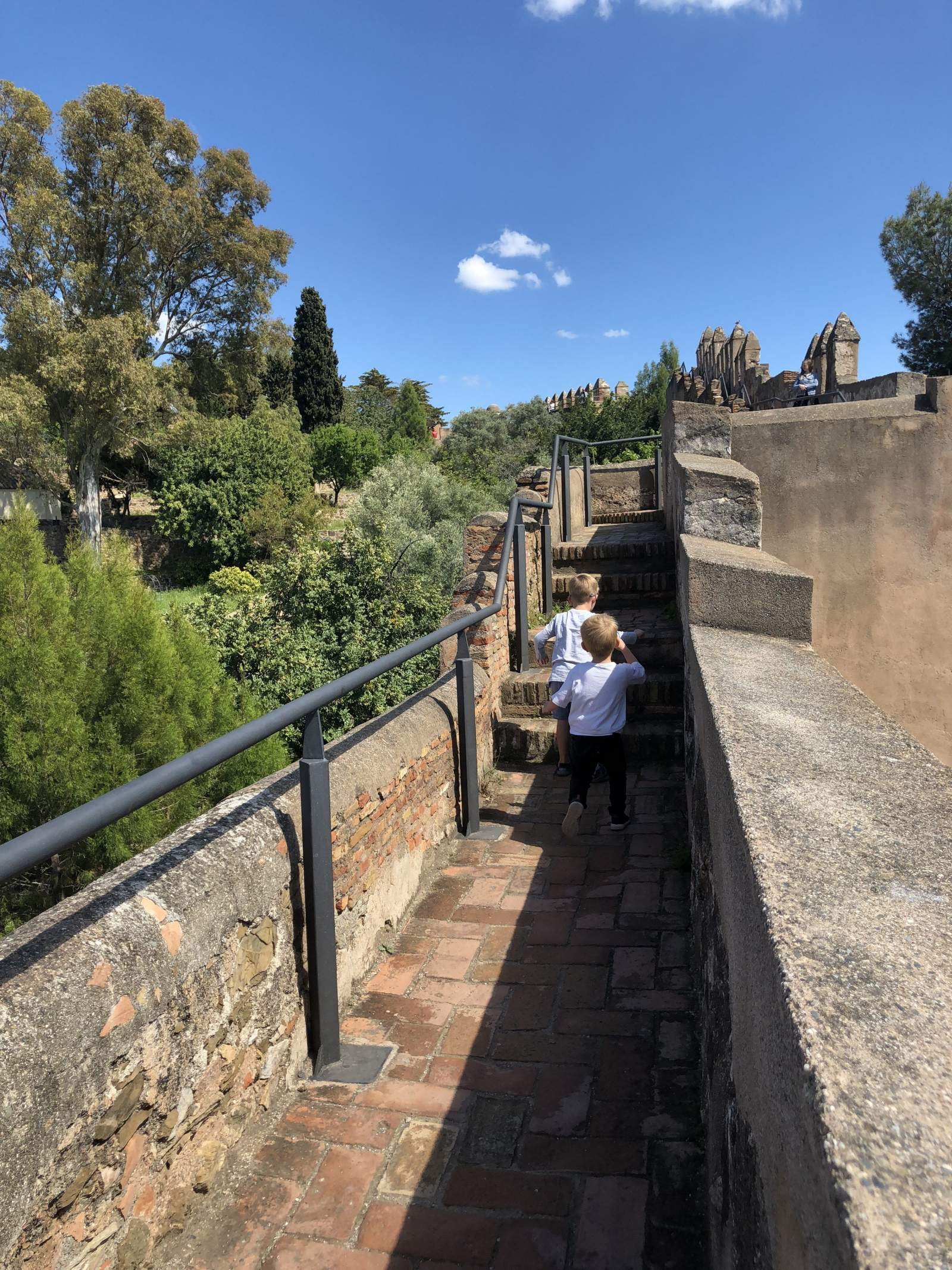 Two boys run along the walls in castillo de gibralfaro