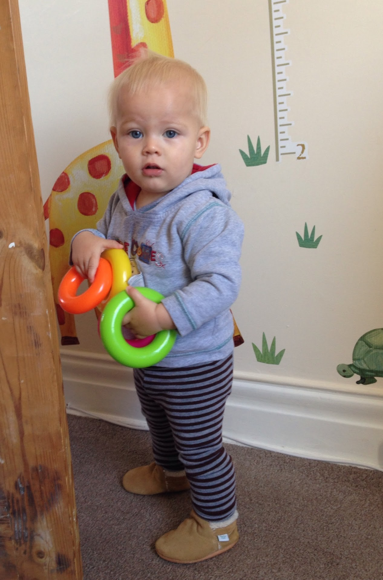 toddler holding plastic stacking rings