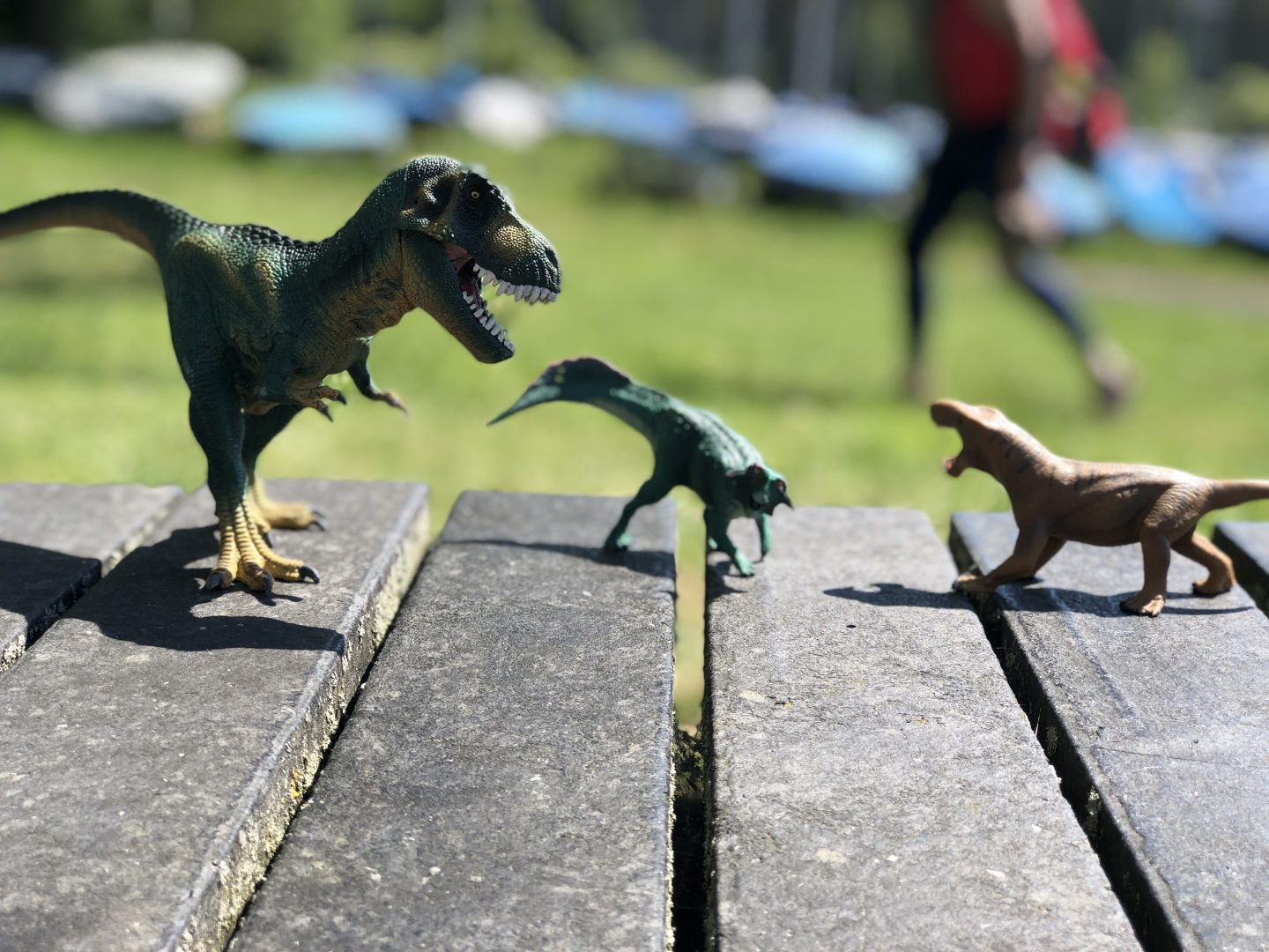 three dinosaurs fighting on a picnic table