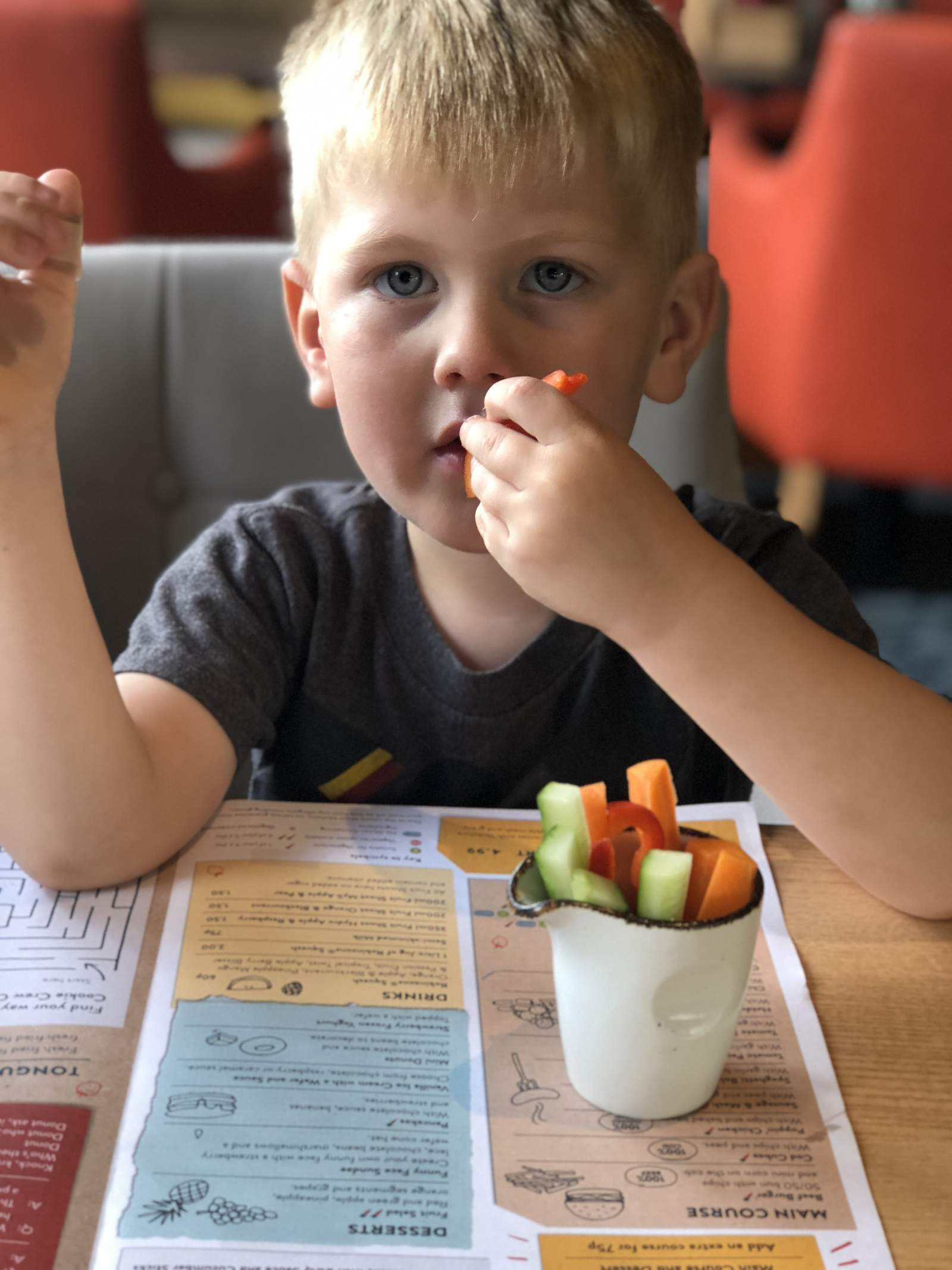 Boy eating vegetable sticks in cookhouse and pub holystone