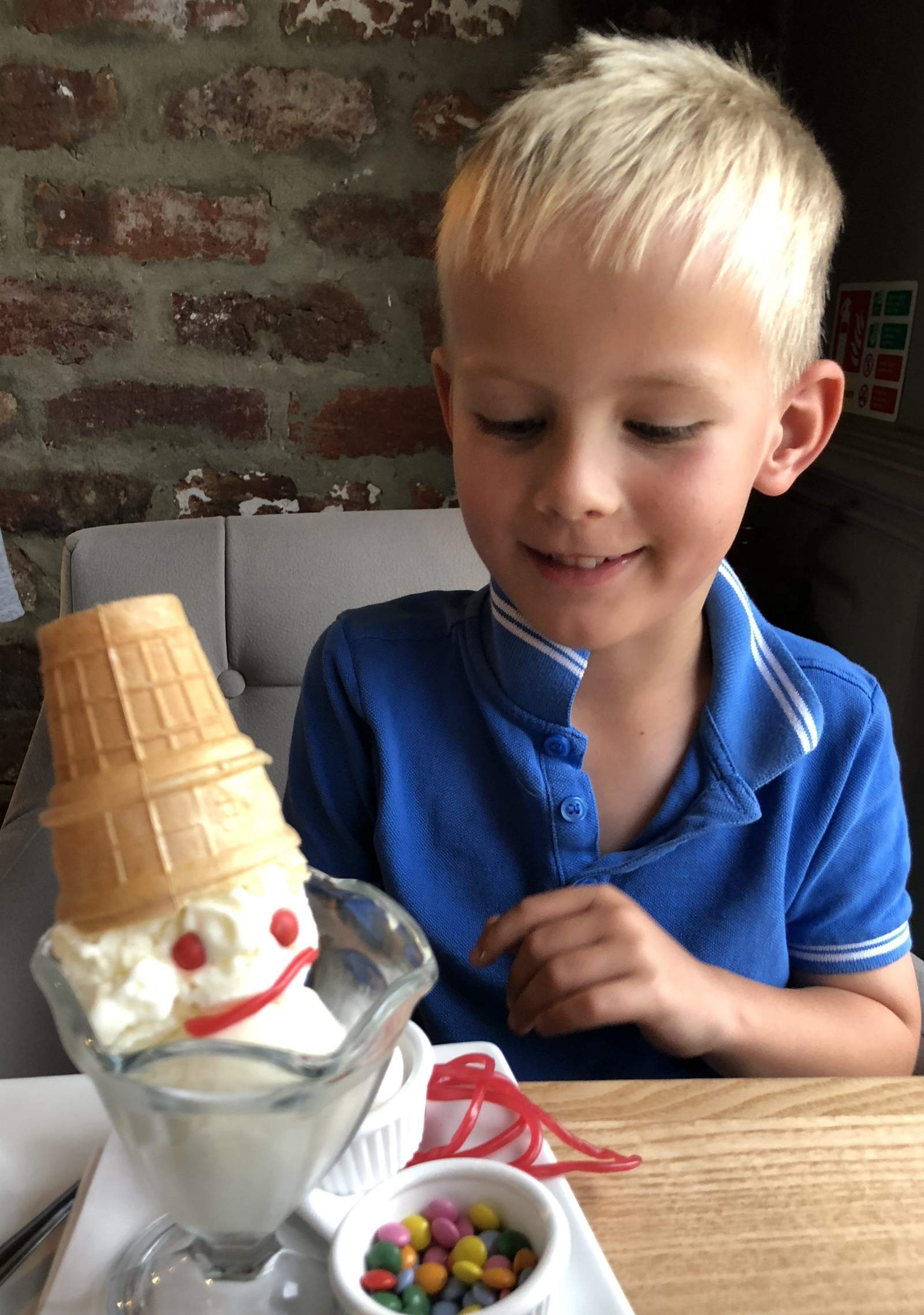 Boy with ice cream dessert in cookhouse and pub holystone