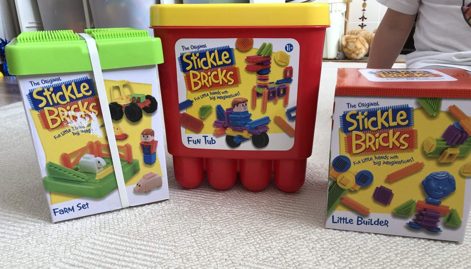 three tubs of stickle bricks in a row