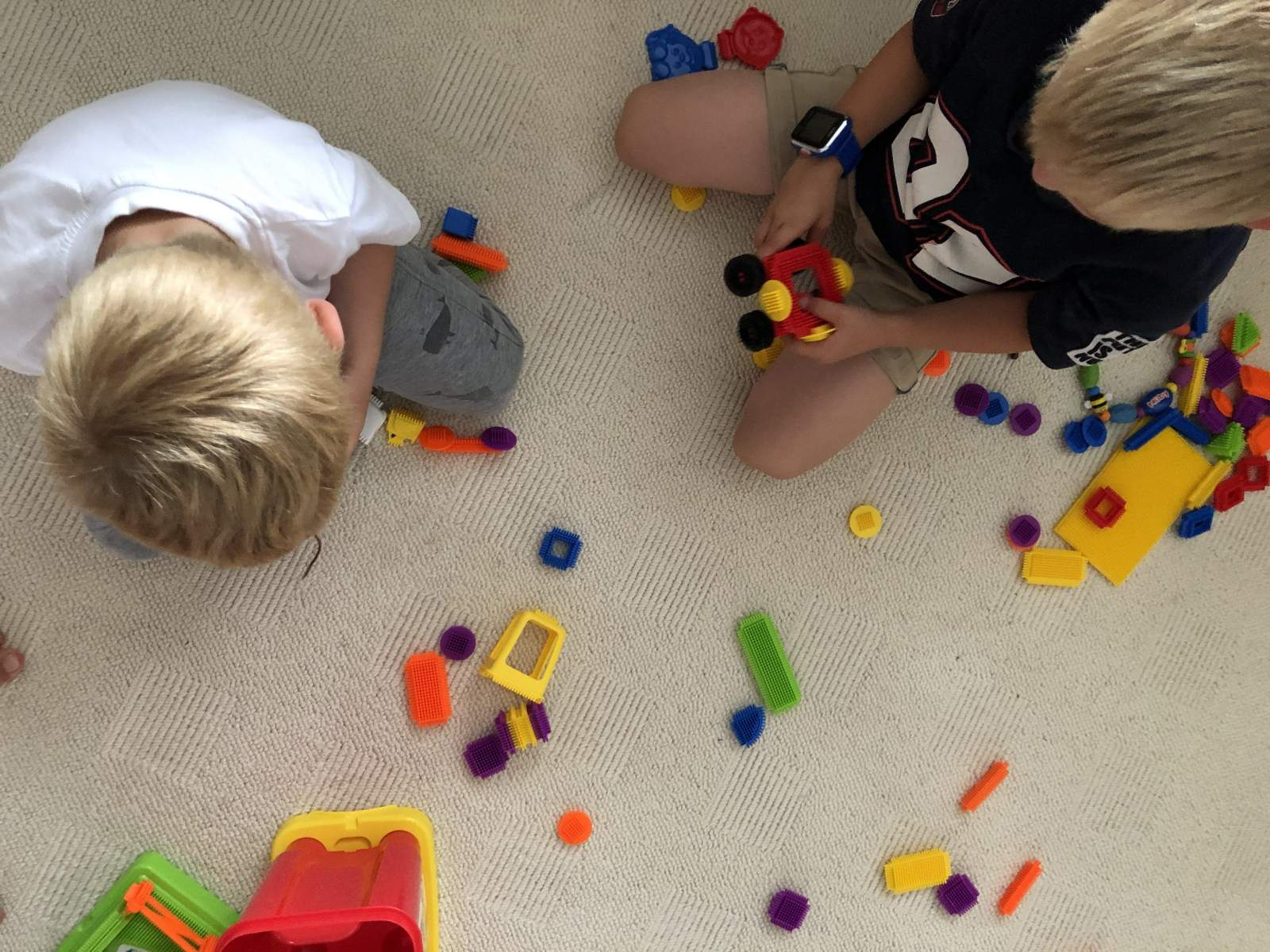 stickle bricks toys on floor two boys playing