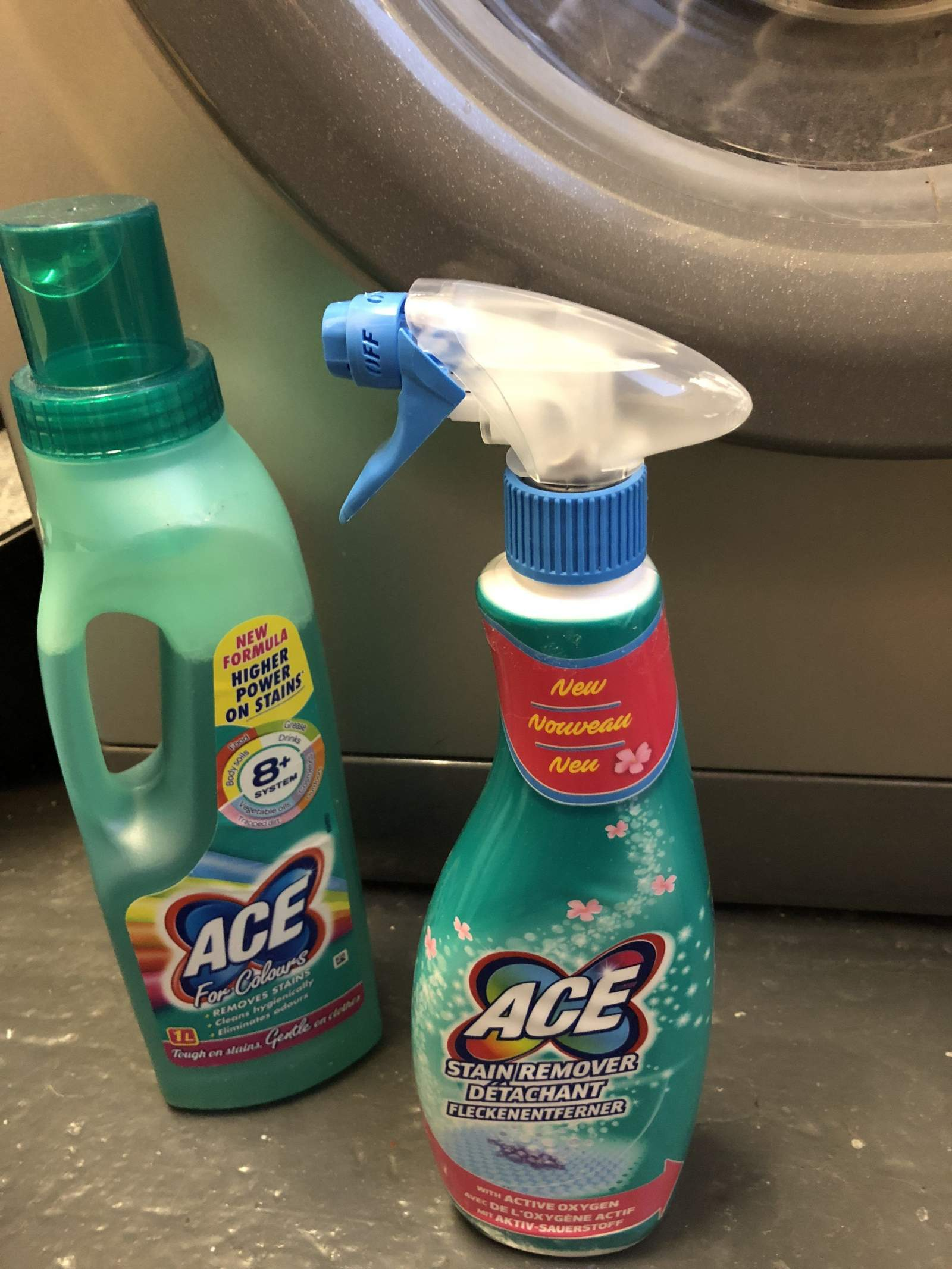 ace bottles in front of washing machine on grey floor