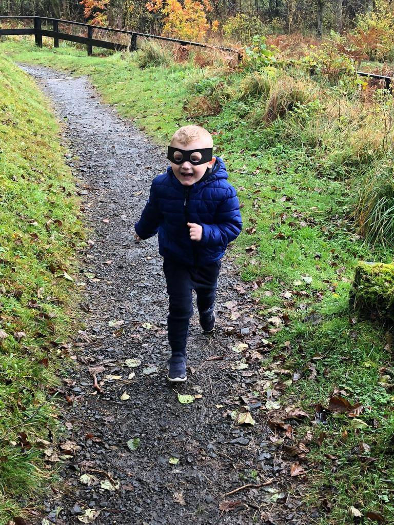 boy wearing mask from highway rat trail at kielder forest running along dirt track