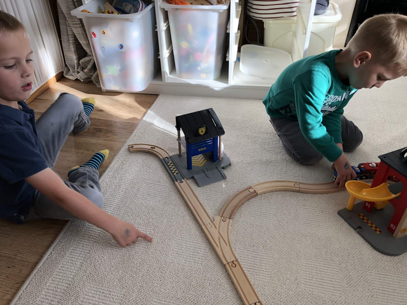 two boys playing with Brio track and police station