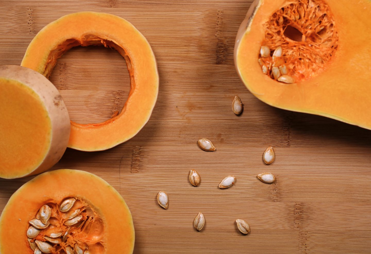 butternut squash sliced on a board with some seeds central