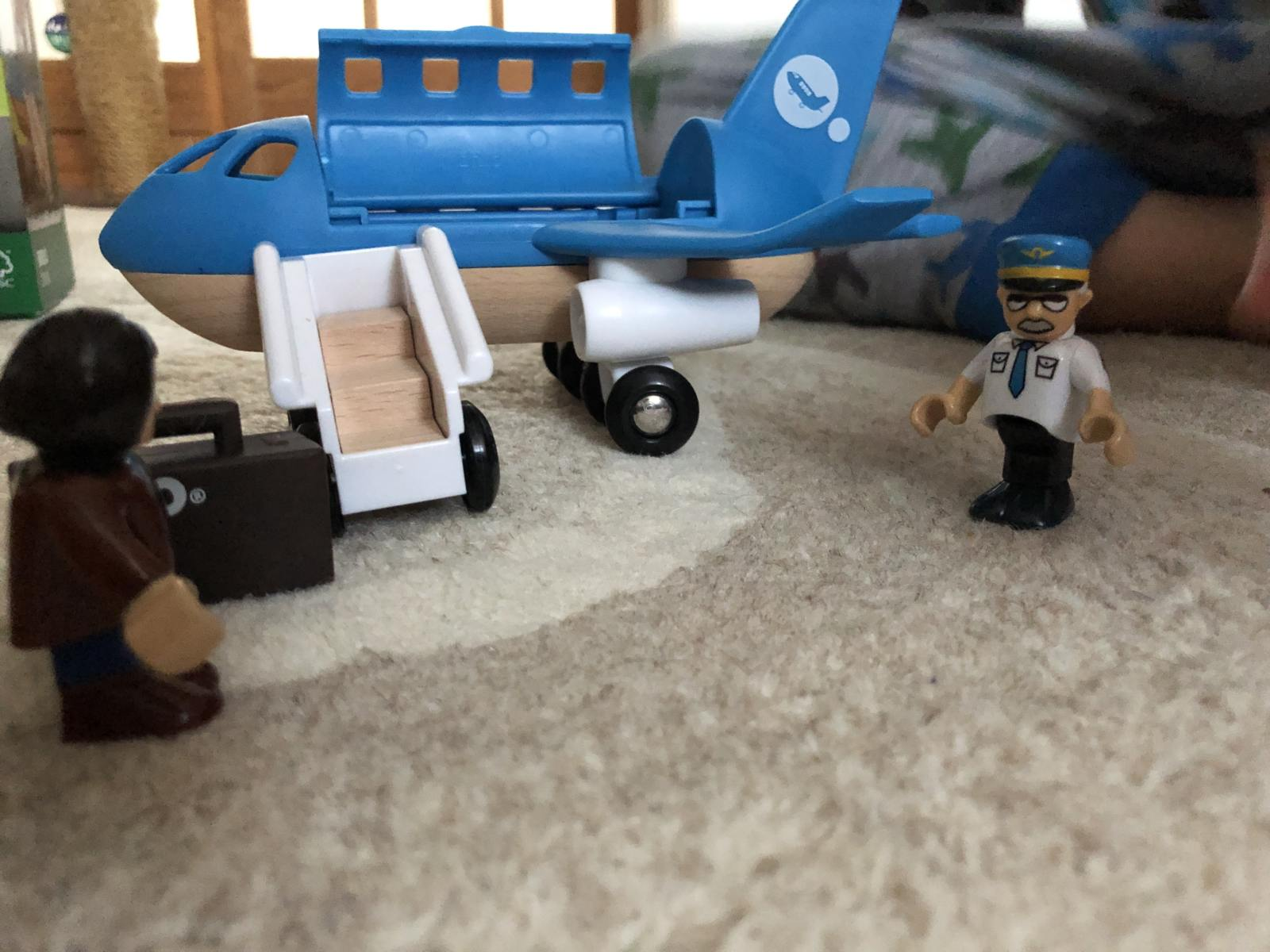brio airplane with suitcase, pilot and passenger outside plane. The plane has stairs and a roof that opens.