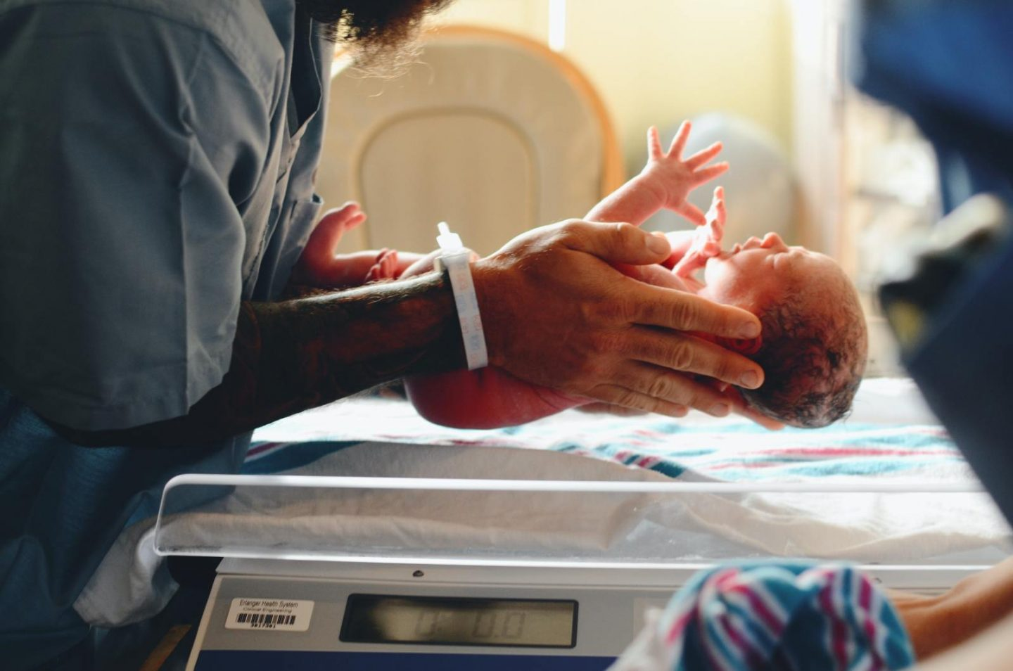 person holding newborn in hands to place the baby on a table