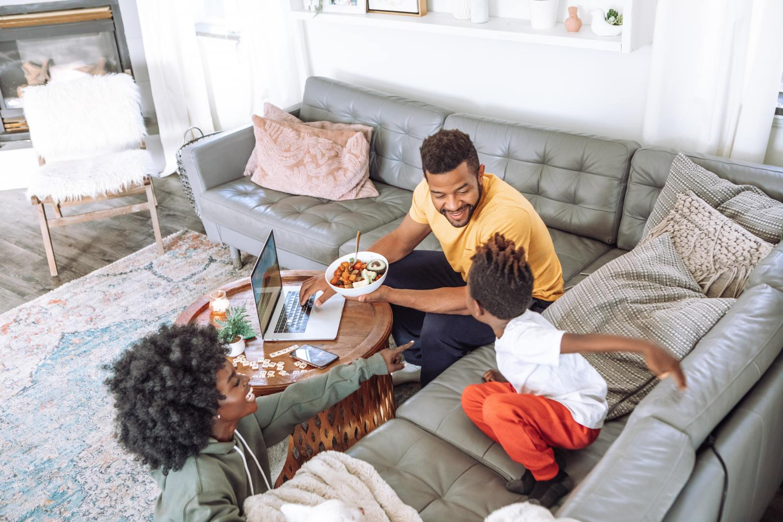 man in yellow crew neck shirt sits on grey sofa smiling at child wearing red trousers, who is sitting on the sofa. Woman wearing grey jacket laughs nearby. The man has a laptop open on the table in front of him.