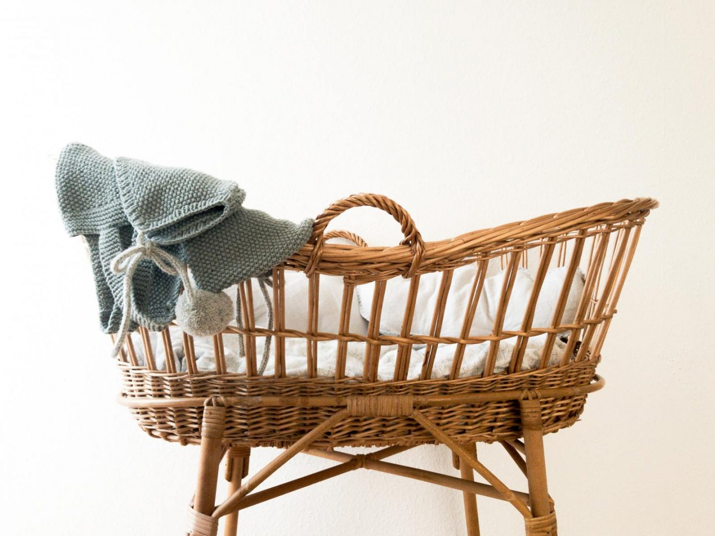 wicker basket with blue shawl draped on one end. Inside the basket is a white mattress and bedding.